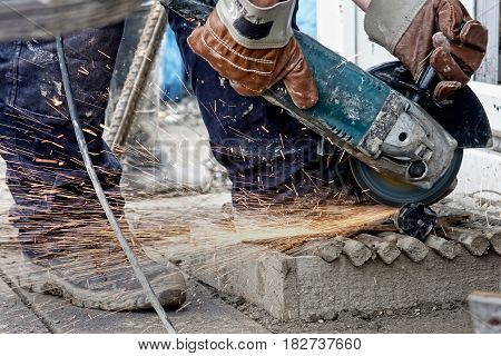A construction worker using a grinder at the site