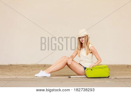 Woman Hitchhiker With Suitcase Sitting On Road