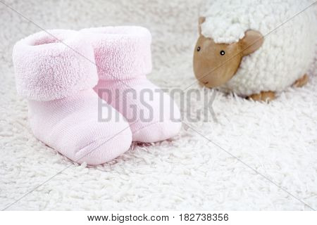 Two pink booties for babies with one toy sheep on the white fur
