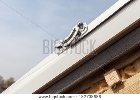 Closeup of element in plastic (mansard) or skylight window on a asphalt shingle roof