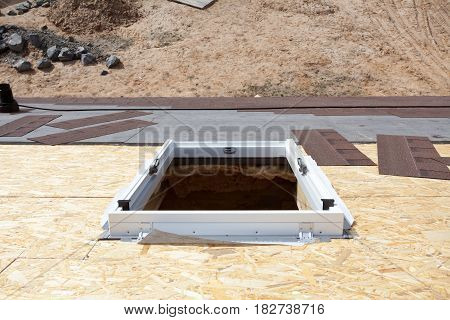Installed frame of new plastic (mansard)or skylight window on a asphalt shingle roof