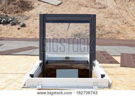 Open plastic (mansard) or skylight window on a asphalt shingle roof