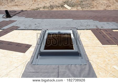 Installing window skylight on a roof with Asphalt Shingles or Bitumen Tiles under construction