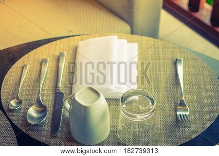 Table appointments- fork,knife,spoon, silk napkin on bamboo mat ( Filtered image processed vintage effect. )