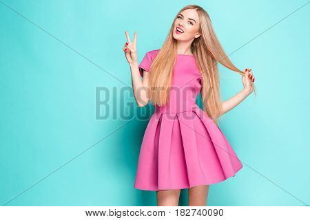 Smiling beautiful young woman in pink mini dress posing and looking at camera. Three quarter length studio shot on blue background.