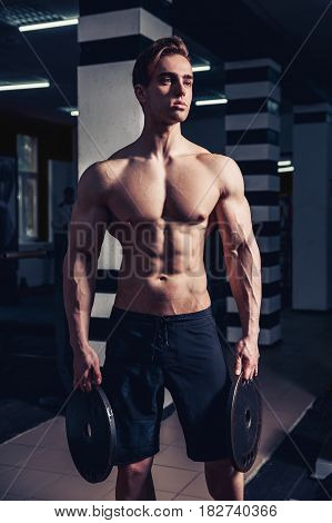 Athlete muscular bodybuilder man posing with dumbbells in gym.