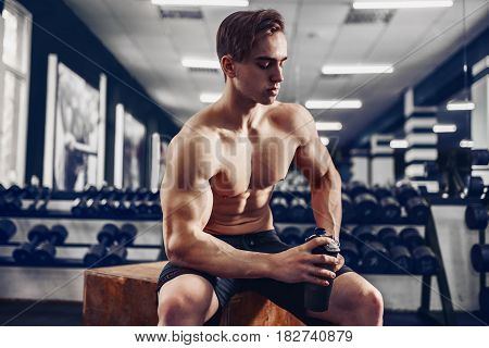 very power athletic guy, relaxing after workouta and hold protein drink in shaker. In the gym
