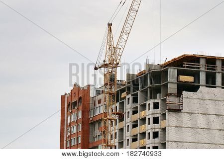 High industrial crane on the construction of a multi-storey residential building