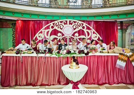 Wedding Couple Sitting On Table At Restaurant With Their Friends, Bridesmaids And Best Mans.