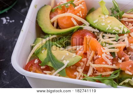Avocado, salmon and cheese salad parmesan. With arugula and salad an iceberg with cherry tomatoes