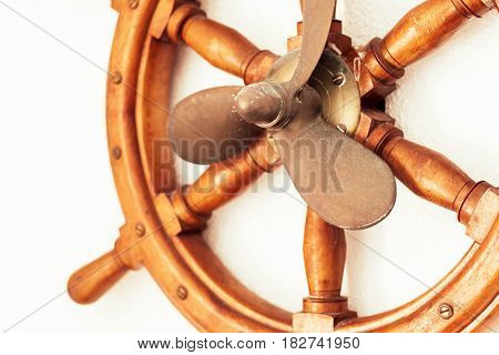 Sea wheel and propeller of a ship on a white wall