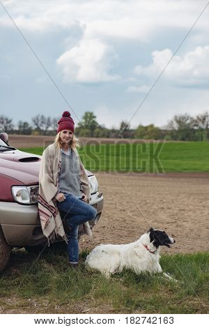 Woman with dog standing by off road vehicle outdoor