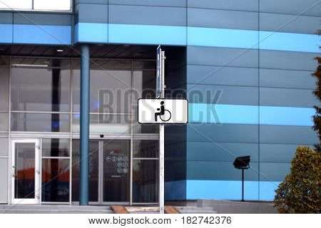 a parking place for disabled people equipped with indicative car signs parked near a public building