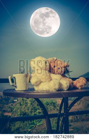 Vintage tone image of two beautiful doll sitting on table with a cup of coffee in the morning blue sky and full moon background. Concept teddy bears couple with love for valentine day.