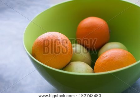 Green apples and oranges in big greed plastic bowl on window sill