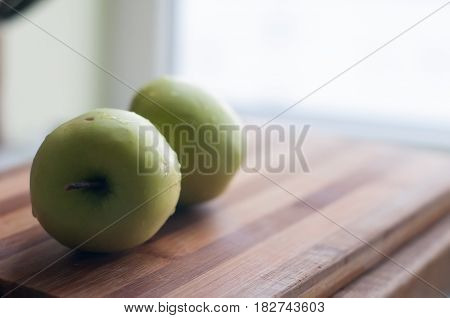 Two green apples lie on wooden cutting board with copy space