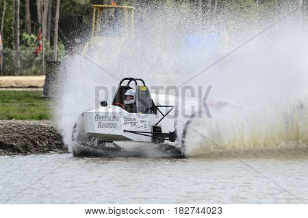 Naples Florida USA - March 3 2012: Swamp buggy spins up wall of water heading onto straightaway