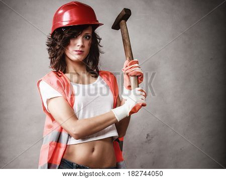 Sex equality and feminism. Sexy girl in workwear safety helmet and orange vest holding hammer tool on gray. Young attractive woman working as construction worker. Studio shot.