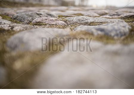 Old cobbled stone pavement of cobblestones in the city with a blurred background. Close-up.