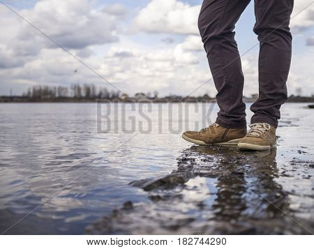 A hipster man stands on the edge by the river's water