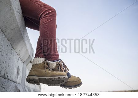 Stylishly dressed girl sits dangling and crossed her legs on a concrete fence against the blue spring sky.
