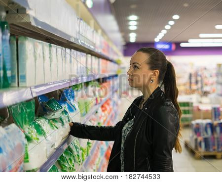 woman housewife searching washing powder and detergents for washing and cleaning the house in the supermarket