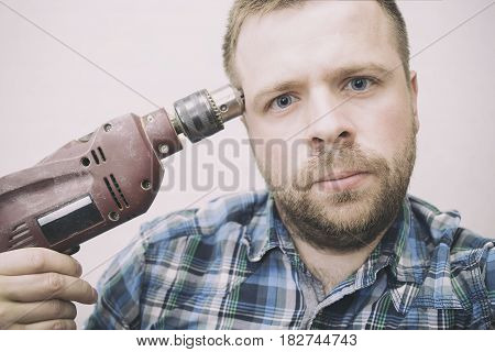 Worker builder carpenter tired at work and wants to commit suicide by shooting himself using an electric drill instead of a gun
