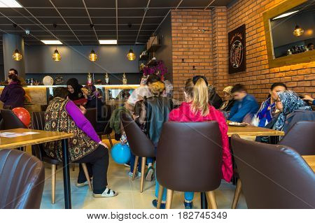Eskisehir Turkey - April 15 2017: People enjoy eat and drinks in the opening of Krepya Cafe. People sitting at a cafe table.