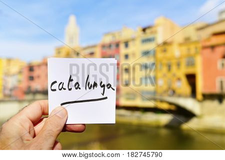 closeup of the hand of a young man holding a paper note with the text Catalunya written in it in Girona, Spain, with the Onyar River and some of the characteristics colorful houses of its Old Town