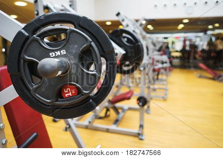 Gym. Barbell for workout indoors. Disks weighing five and fifteen kilograms.