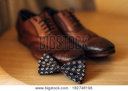 Wedding accessories of the groom - a bow tie and brown shoes.