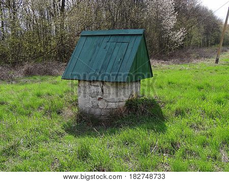 Old well standing in the green grass in the garden