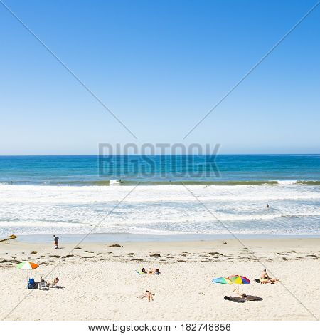 Beach and white sand. The turquoise water of the ocean lagoon. Blue sky.