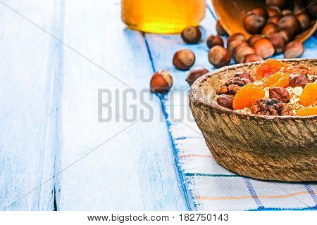 Homemade granola in rustic wooden bowl. Hazelnuts and honey on the background