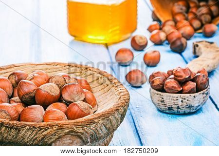 Hazelnuts in shell scattered on blue plank table and in wood bowl. Shelled nuts in wooden spoon. Honey jar next to the nuts