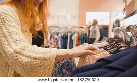 Red hair woman in a clothing store chose a dress - shopping concept, close up