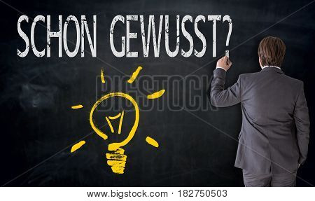 Businessman is painting light bulb and schon gewusst? (in german already known?) On blackboard concept.