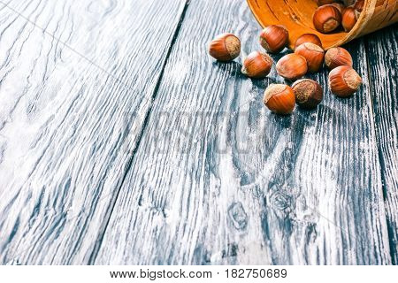 Hazelnuts in shell scattered on black wood table