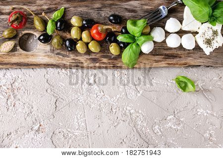 Mediterranean appetizer antipasti board with green black olives, feta cheese, mozzarella, capers, pepper, basil over beige concrete texture background. Top view with space