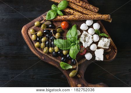 Mediterranean appetizer antipasti board with green black olives, feta cheese, mozzarella, capers, pepper, basil with grissini bread sticks over black wood burnt background. Top view with space
