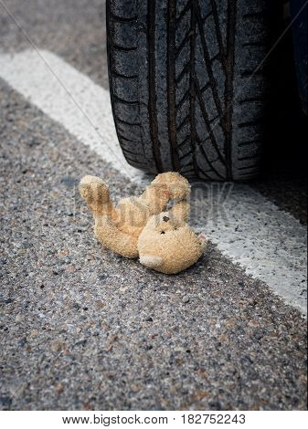 soft toy bear in the blood under the car wheels
