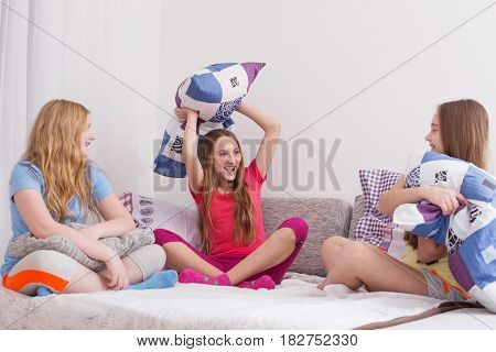 teenage girls having fun and fighting with pillows
