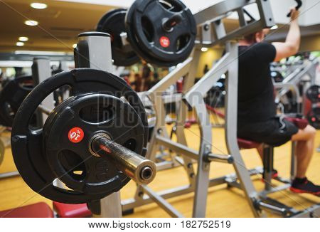 The athlete is engaged in the gym lifting heavy weight in the simulator. Barbell for workout indoors.