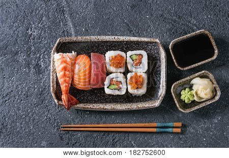 Sushi Set nigiri and sushi rolls in dark ceramic plate with soy sauce and chopsticks over black stone texture background. Top view with space. Japan menu