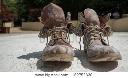 Old brown work boots covered in concrete worn by a woman