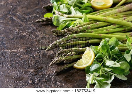 Bundle of young raw uncooked organic green asparagus with green salad leaves, sliced lemon and sea salt over brown texture background. Close up. Healthy eating