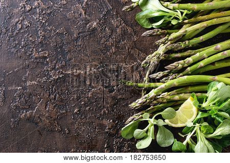 Bundle of young raw uncooked organic green asparagus with green salad leaves, sliced lemon and sea salt over brown texture background. Top view. Healthy eating