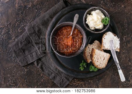Bowl of red caviar with spoon served with sliced bread, butter and herbs on black wooden chopping board over brown texture background. Top view with space