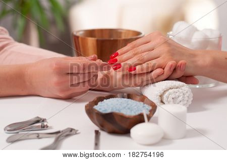 Manicure Concept. Beautiful Woman's Hand Wiith Red Nails In The Spa.