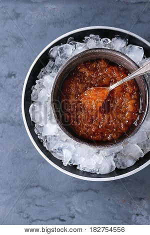 Bowl of red caviar on ice with spoon served over gray blue texture background. Top view with space